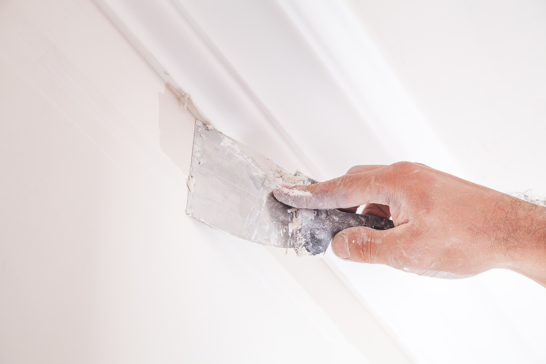 Plastering wall with spatula.